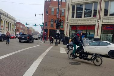A cyclist at Milwaukee, Damen and North avenues intersection in Wicker Park.