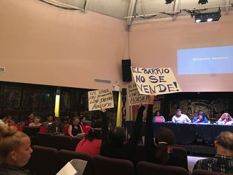 Protestors raised signs as Community Board 11 members spoke at the meeting Tuesday.