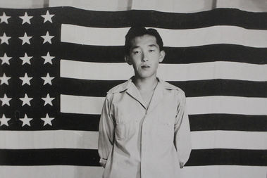 This image of a Japanese-American internee in front of a U.S. flag was taken by an uncredited photographer.