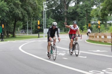Bicyclists wave as they ride on East Drive in Prospect Park. Starting next week, cars will be banned completely from all roadways inside the park.