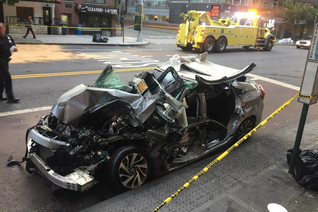 A Honda lay badly damaged after getting hit by a DOT truck, not the one in the background, officials said.