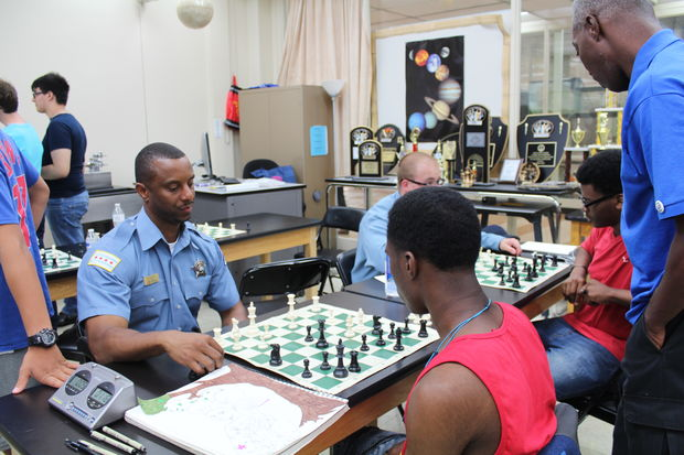 A Chicago police officer plays a game of chess with Chicago Christian Academy students at Whitney M. Young Magnet High School.