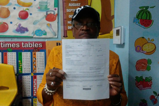 Day Care assistant Denise Burke holds the health department citation for harboring roosters.