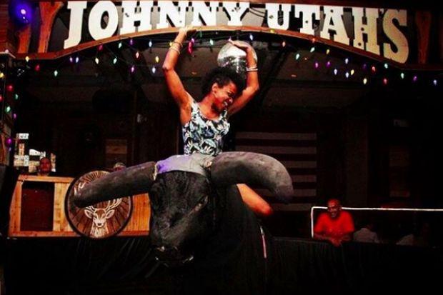 A Johnny Utah's patron rides the bar's mechanical bull.