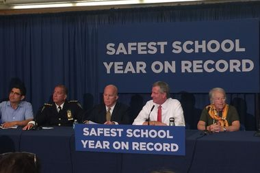 Mayor Bill de Blasio, flanked by the NYPD commissioner and Schools Chancellor, announcing the drop in crime at city schools.