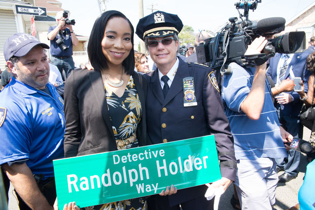 Randolph Holder's fiancee, Mary Muhammad, holds the street sign with NYPD Chief of Community Affairs Joanne Jaffe.