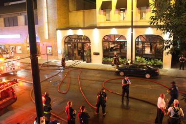 Firefighters clean up after dousing a fire at the Balena Restaurant building at 1633 N. Halsted St.