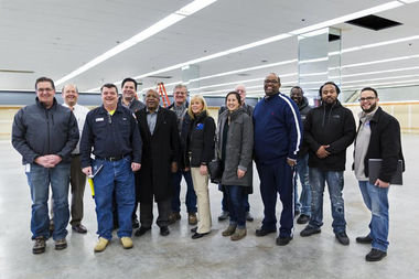The Rev. Corey Brooks, in blue jacket with white stripe, is leading a team that is converting a vacant Walgreens into the temporary home for his nonprofit that provides business classes and job training.