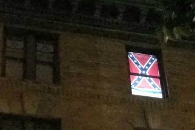 A pair of Confederate flags hung in the windows of an East Eighth Street building near Avenue D.