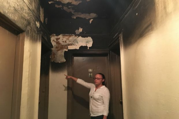 Natasha Tosca in her building's hallway, showing damage left from a fire in early July.