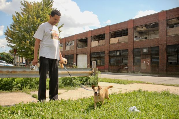 Daniel Roman walks his dog, Bubba, past the vacant Zenith factory at the end of his block.