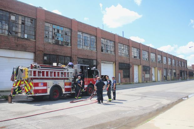 Firefighters remain on scene after an Aug. 22 fire consumed a factory on the Zenith plant grounds. The 6000 block of West Dickens will remain closed to pedestrians and traffic due to concerns about