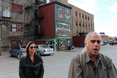 Lauren Ditka and James Geier of 555 International in front of a mural showing a cross-section of the Horween Leather Company within, as painted by Sick Fisher