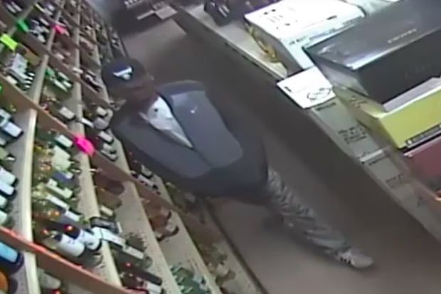 An armed robber in a Chicago Bulls baseball cap made off with $1,500 in cash after holding up a Grand Street liquor store, the NYPD said.