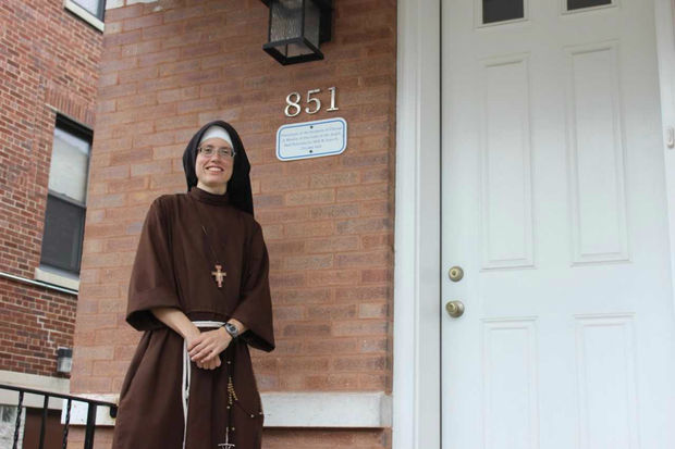Sister Stephanie Baliga (pictured) stands in front of the mission's renovated two-flat.