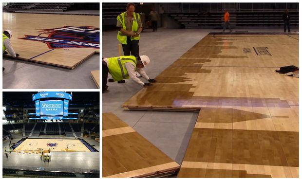 Workmen assemble the basketball floor for DePaul University at Wintrust Arena.