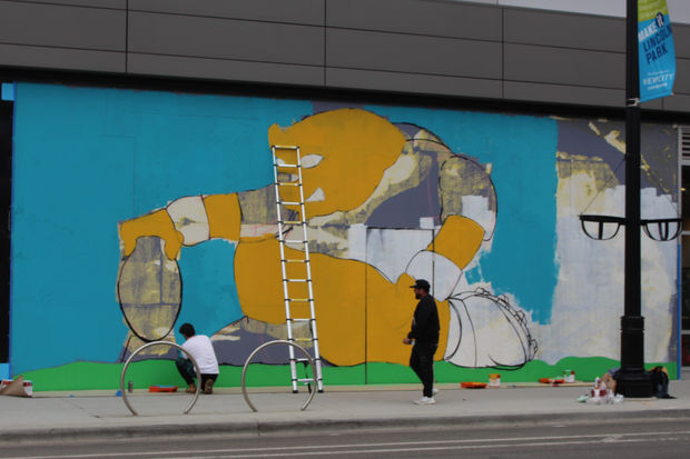 JC Rivera and an assistant block out the forms for a Chicago Bears mural at the NewCity shopping center.