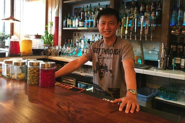 Mark Lu, co-owner of Porto Salvo, behind the restaurant's bar.