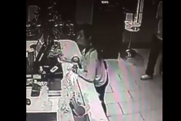 Surveillance footage shows a woman walking into Youyo Frozen Yogurt and stealing its tip jar.