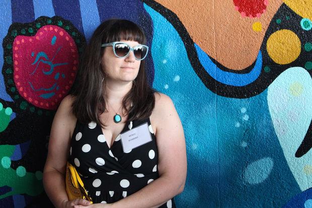 Renee Robbins stands in front of her mural