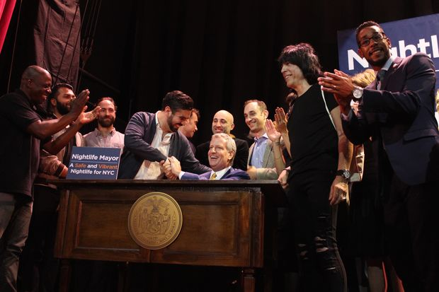 Mayor Bill de Blasio signed the legislation at House of Yes Tuesday night in Bushwick surrounded by Marky Ramone, drummer for The Ramones, and jazz double-bassist Ron Carter.