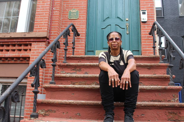 Evette Simmons sits on the stoop of the building she inherited from her grandfather.